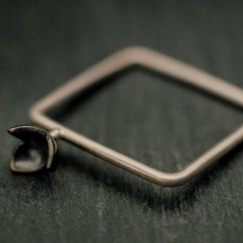 Bague carrée en fil d'argent rond, avec une petite fleur à trois pétales soudée en relief sur le corps de bague
