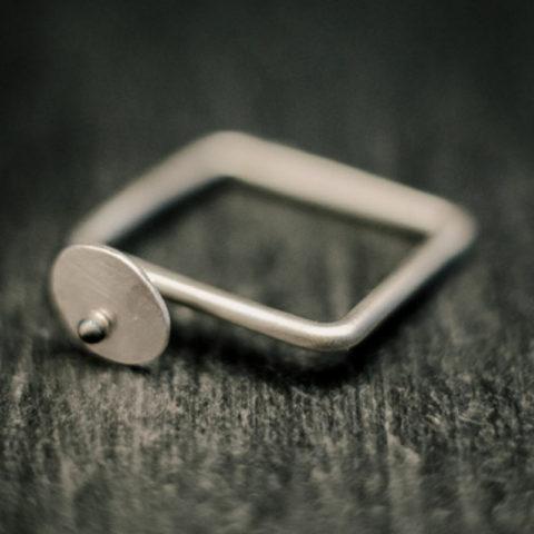 Bague carrée en fil d'argent rond, avec en relief une pastille ovale martelée ornée d'une petite bille