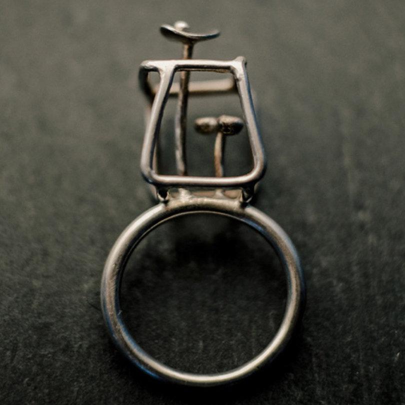 bague en argent composée d'un anneau en fil rond épais surmonté de deux fleurs stylisées à l'intérieur d'un cube irrégulier en fil d'argent.