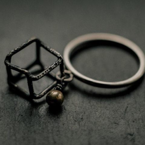 bague composée d'un cube irrégulier en fil d'argent noirci et d'une petite bille en or, suspendus à un petit anneau soudé sur le corps de bague en fil d'argent rond