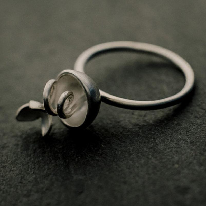 bague en argent composée d'une petite coque d'où sort une sorte de vrille surmontée d'une fleur à trois pétales, anneau fil d'argent rond