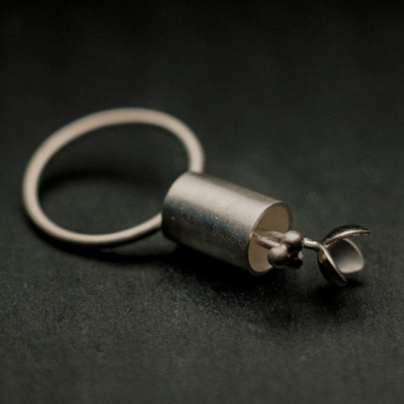 """bague en argent composée de deux fleurs stylisées sortant d'un petit """"pot"""" cylindrique, anneau fil d'argent rond."""
