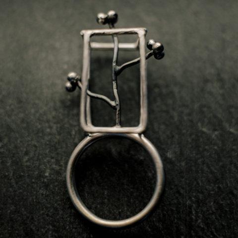 bague en argent composée d'un corps de bague en fil rond et d'un parallélépipède en fil d'argent à l'intérieur duquel s'élève une petite branche sinueuse donnant sur trois petites grappes à trois billes.