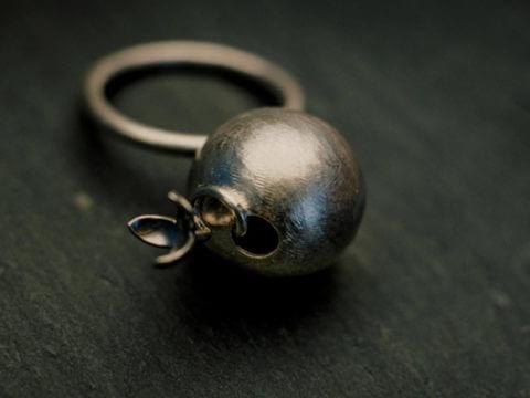bague composée d'une boule d'où s'échappe une petite fleur sur une tige tortueuse, anneau fil rond.