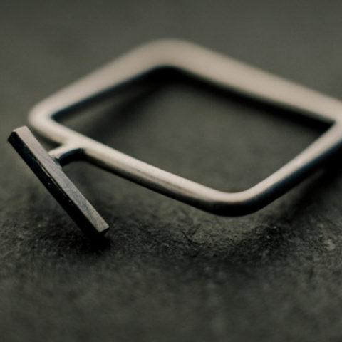 Bague carrée en fil d'argent rond, avec, en relief, une petite tige de section carrée soudée légèrement de biais.