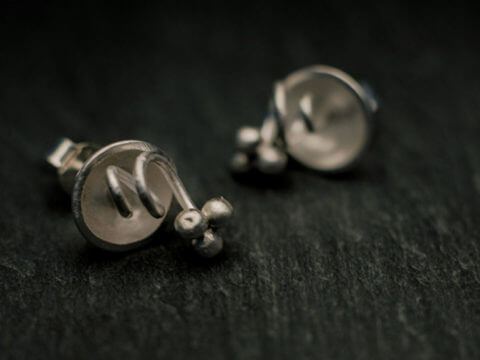 boucles d'oreilles puces en argent composées de petites coques d'où sortent de fines tiges enroulées comme des vrilles et surmontées de petites grappes à trois billes.