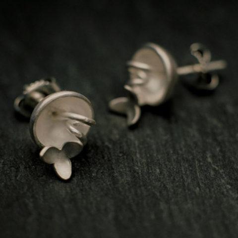 boucles d'oreilles puces en argent composées de petites coques d'où sortent de fines tiges enroulées comme des vrilles et surmontées de petites fleurs à trois pétales.
