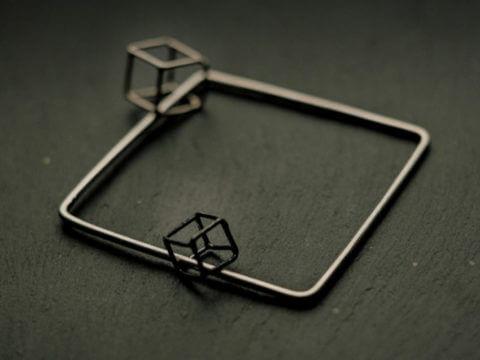 bracelet carré en fil d'argent rond épais sur lequel circulent deux cubes en fil d'argent et argent noirci de taille différentes.