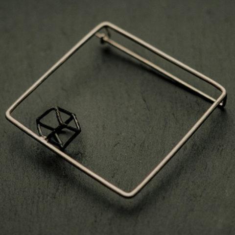 broche carrée en fil d'argent sur laquelle est soudée un petit cube en fil d'argent noirci.