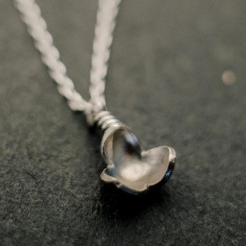 pendentif en argent composé d'une petite fleur à trois pétales, monté sur chaîne