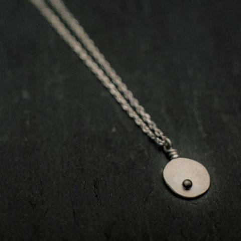 pendentif en argent composé d'une pastille ovale martelée ornée d'une petite bille, monté sur chaîne.