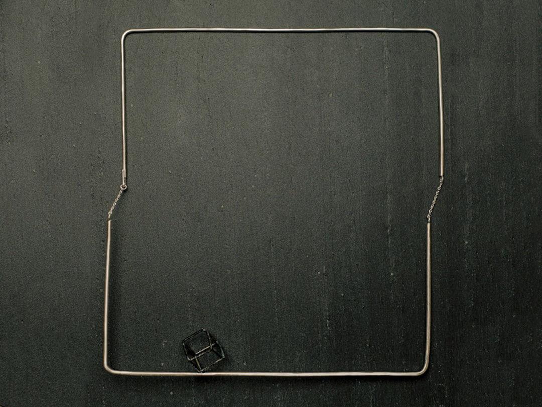 Collier carré en argent, articulé grâce à deux petites chaines de chaque côté. Cube en argent texturé et noirci.