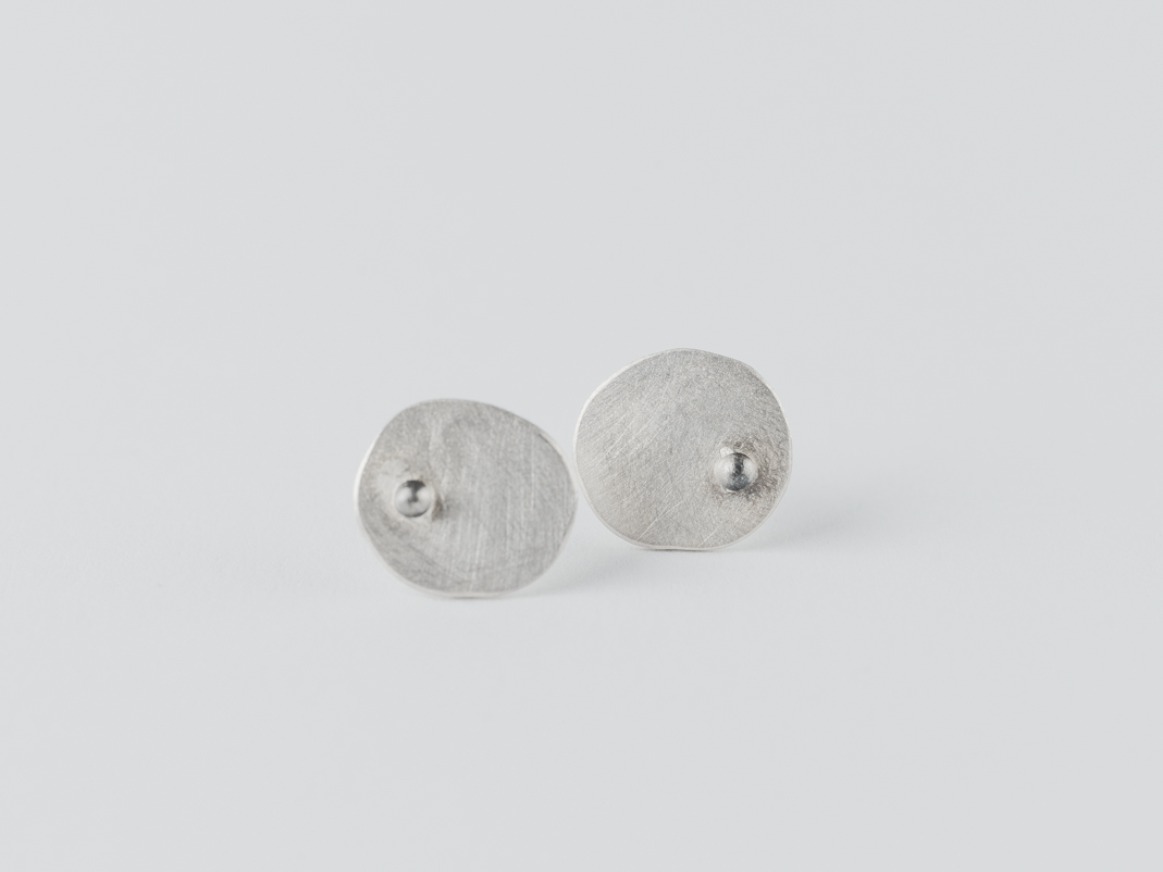 boucles d'oreilles puces en argent composées de petites pastilles ovales martelées ornées d'une petite bille.