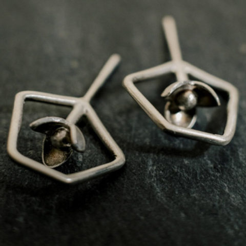 boucles d'oreilles puces composées de petites fleurs à l'intérieur de formes géométriques en fil. Le motif se positionne perpendiculairement à l'oreille.