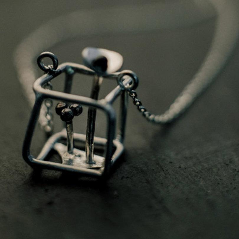 pendentif en argent monté sur une longue chaîne et composé de deux fleurs stylisées à l'intérieur d'un cube irrégulier en fil d'argent