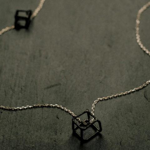Sautoir sur chaîne en argent avec trois cubes en argent texturé et noirci (deux petits fixes et un grand mobile).