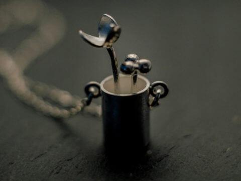 """pendentif en argent composé de deux fleurs stylisées sortant d'un petit """"pot"""" cylindrique, monté sur longue chaîne en argent."""