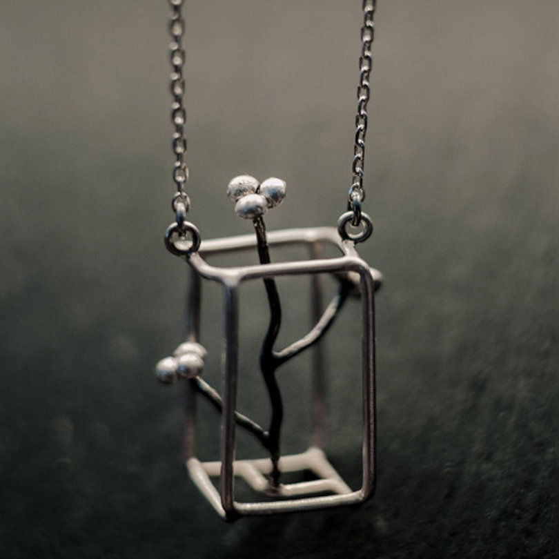 pendentif monté sur longue chaîne en argent et composé d'un parallélépipède en fil d'argent à l'intérieur duquel s'élève une petite branche sinueuse donnant sur trois petites grappes à trois billes.