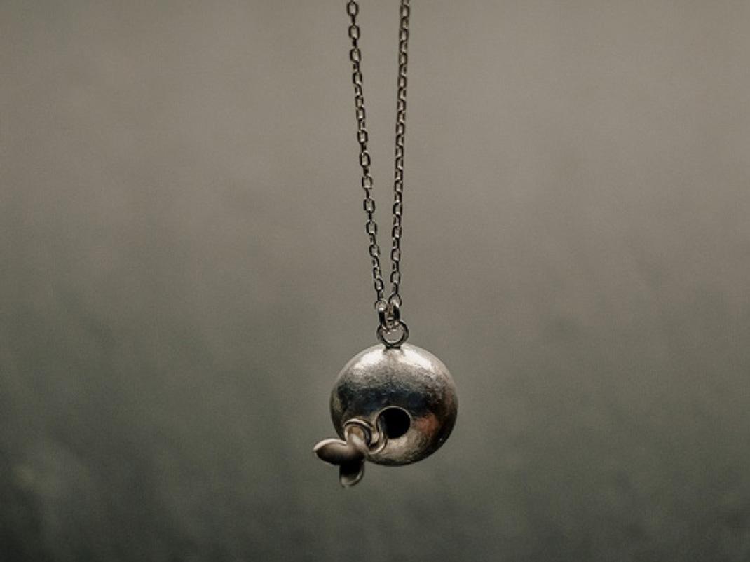 pendentif en argent composé d'une boule d'où s'échappe une petite fleur sur une tige tortueuse, monté sur une longue chaîne.