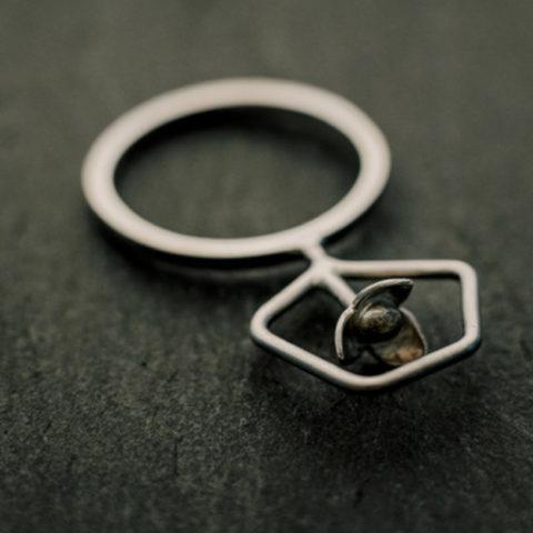 bague en argent composée d'une petite fleur à l'intérieur d'une forme géométrique en fil. Le motif se positionne perpendiculairement au corps de bague (fil de section carrée)