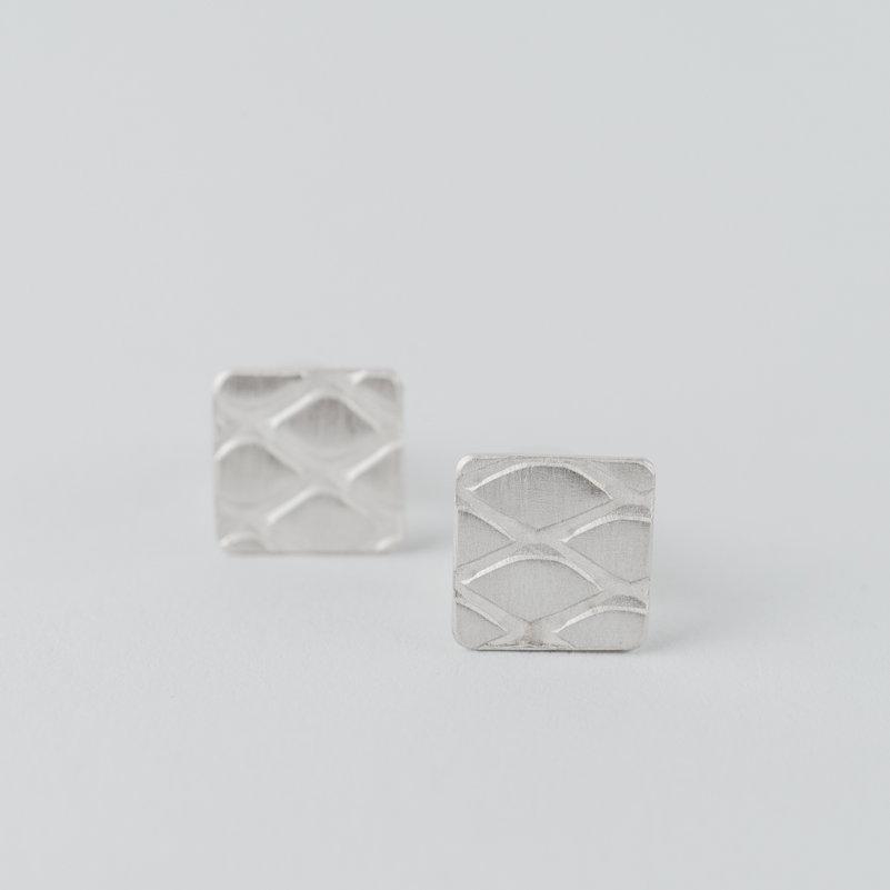 boucles d'oreilles puces en argent composées de petits carrés avec un motif grillage incrusté