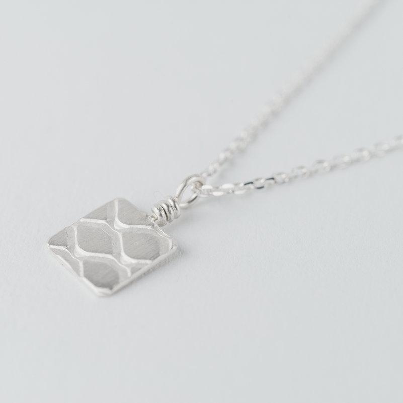 Collier en argent composé d'un petit pendentif carré avec motif grillage incrusté monté sur chaîne