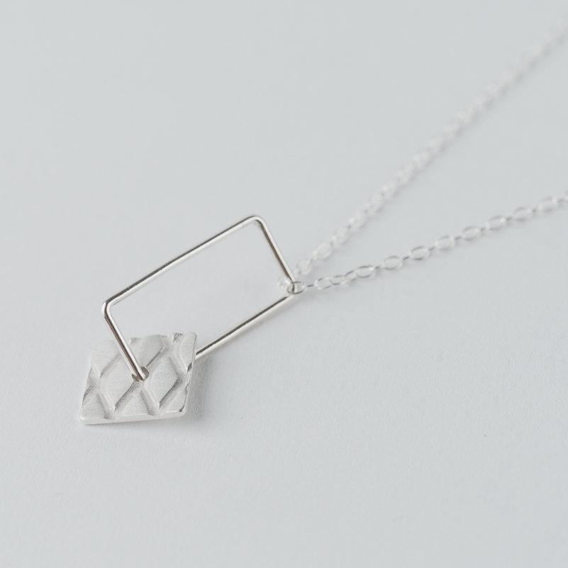 petit pendentif en argent composé d'un rectangle en fil et d'un carré avec motif grillage incrusté, monté sur chaîne.