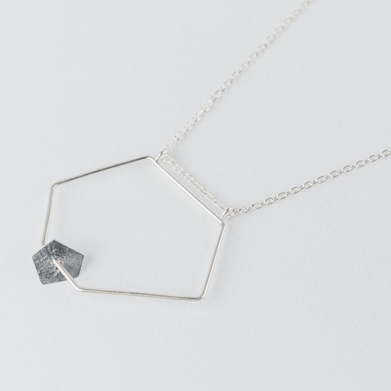 collier composé d'un grand pendentif géométrique en fil d'argent sur lequel circule une pastille de forme pentagonale en argent noirci et texture froissée, monté sur chaîne argent.