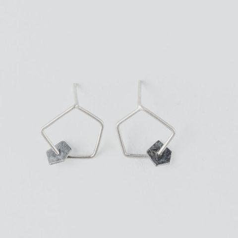 boucles d'oreilles sur clous composées d'une forme géométrique en fil et d'une petite pastille mobile de forme pentagonale en argent noirci, texture froissée