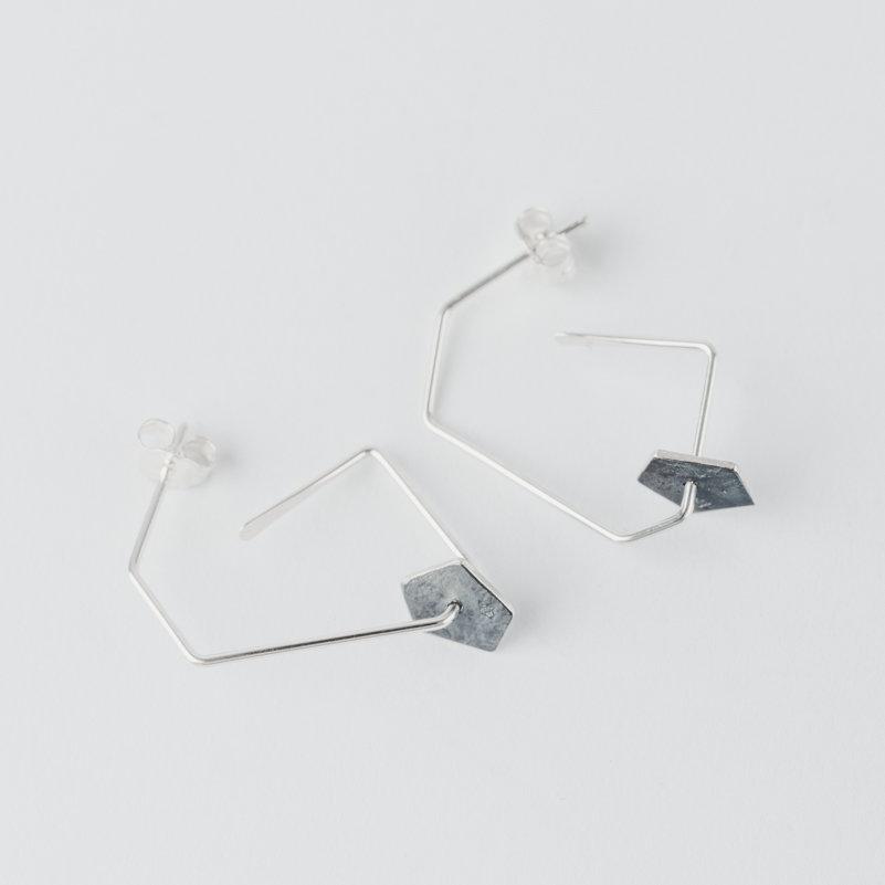 boucles d'oreilles pendantes composées d'une forme géométrique en fil sur laquelle circule une pastille de forme pentagonale en argent noirci et texture froissée.