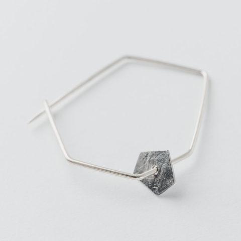 broche géométrique en fil d'argent et pastille mobile de forme pentagonale en argent noirci et texture froissée.