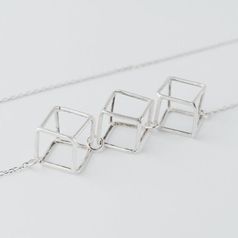 Sautoir composé de trois cubes en fils d'argent montés sur longue chaîne en argent.