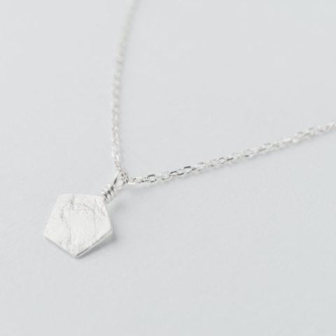 """Collier en argent composé d'un pendentif de forme géométrique, effet de matière """"froissé"""", monté sur chaîne"""