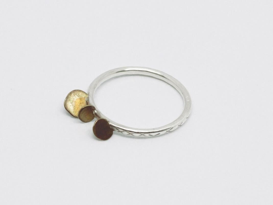 anneau fil rond en argent ciselé sur lequel sont soudées de manière irrégulière trois pastilles en laiton martelé.