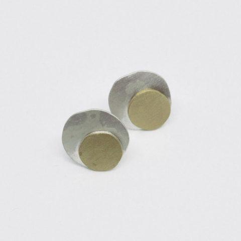 boucles d'oreilles puces composées de deux pastilles martelées en argent et laiton, montées sur clous.