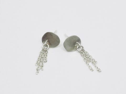 boucles d'oreilles puces montées sur clous composées de pastilles ovales irrégulières en argent martelé sur lesquelles sont fixés de fins pompons de chaînes en argent