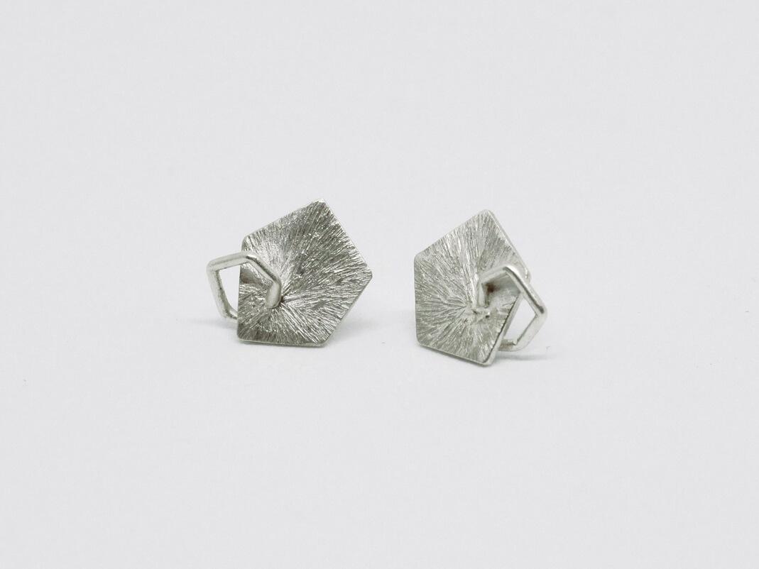 Boucles d'oreilles puces en argent composées de pastilles géométriques de formes pentagonales à la surface striée sur lesquelles sont soudées de petits pentagones en fil d'argent
