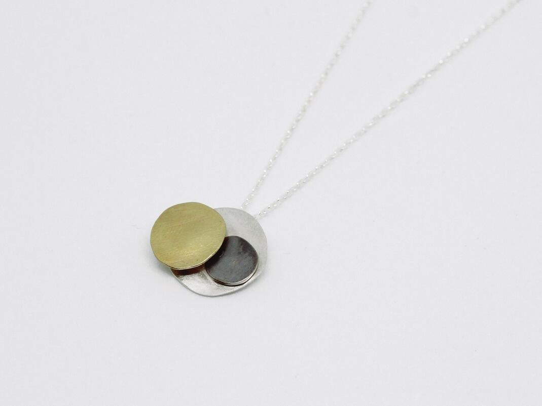 pendentif composé de trois pastilles martelées, en argent, argent noirci et laiton (en relief), monté sur chaîne argent.
