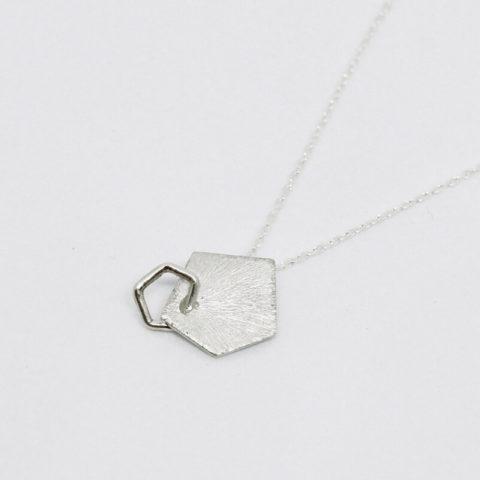 pendentif en argent composé d'une pastille géométrique de forme pentagonale à la surface striée sur laquelle est soudée un petit pentagone en fil d'argent, monté sur chaîne en argent.