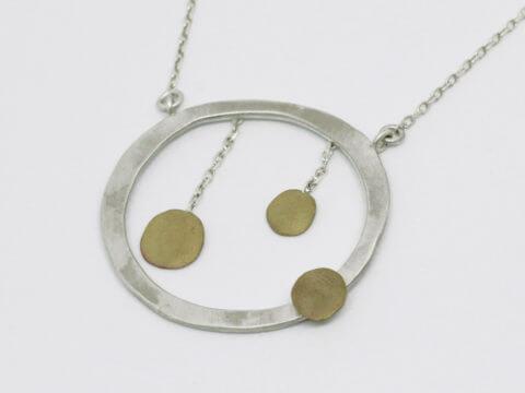 sautoir en argent et laiton composé d'un pendentif rond monté sur chaîne