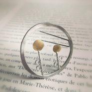broche ronde en argent et laiton composée de deux fleurs stylisées dans un cercle irrégulier en argent martelé .