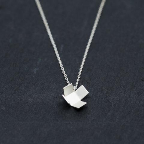 petit pendentif en argent composé d'un cube aux faces ouvertes et monté sur une fine chaîne en argent.