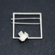 broche en argent composée d'un carré en fil d'argent de section carrée sur lequel est soudé un cube aux faces ouvertes.