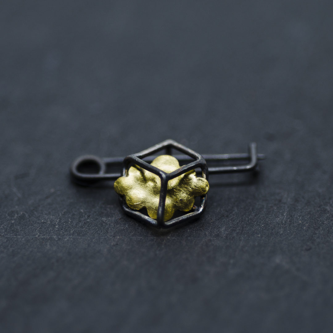 broche composée d'un cube en fil d'argent noirci à l'intérieur duquel se trouve en petit nuage en laiton et monté sur une épingle en argent noirci.